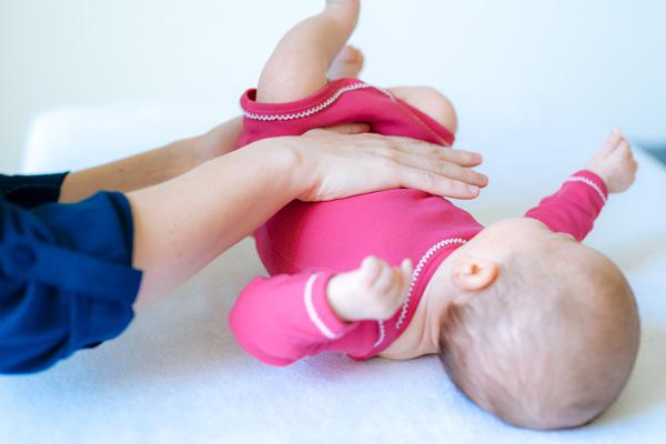 Baby im pinken Strampler wird von Kinderosteopathin behandelt